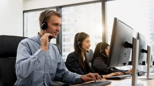 Call center operator agent in a headset with microphone consulting client online close up, Focus on the face