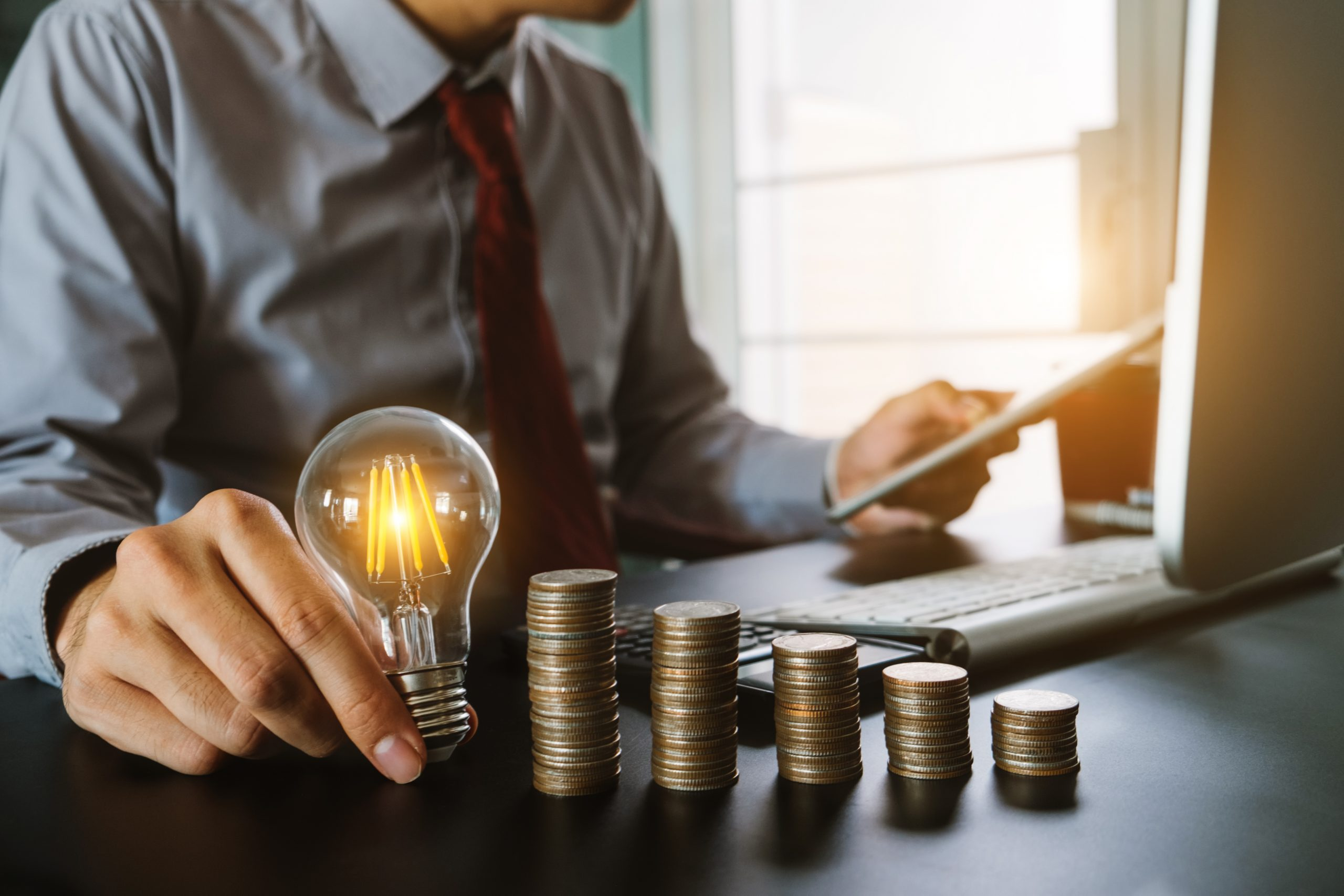 business hand holding lightbulb with using laptop computer and money stack in office. idea saving energy and accounting finance concept in morning light M